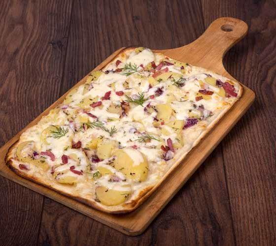 Flammkuchen mit Kartoffelspalten, geräuchertem Schinkenspeck, Gouda und frischen Kräutern